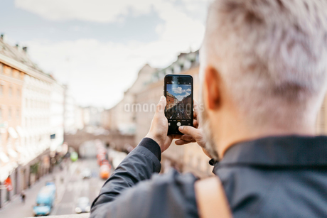 Man taking photograph of street in Stockholm, Swedenの写真素材 [FYI02209313]