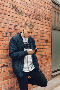 Teenage boy leaning on a brick wall looks at his phone in Swedenの写真素材 [FYI02209351]
