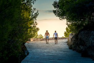 Greece, Cephalonia, Assos, Tourists walking on footpathの写真素材 [FYI02209369]