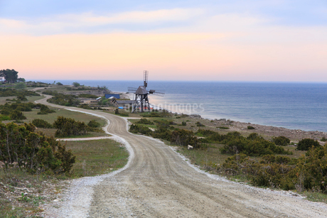 Rural road by beach and windmill in Jordham, Swedenの写真素材 [FYI02209372]