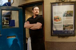 Fishmonger standing outside of storeの写真素材 [FYI02209383]