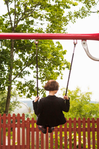 Finland, Pirkanmaa, Tampere, Young woman swinging in back yardの写真素材 [FYI02209430]