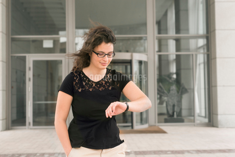Israel, Tel Aviv, Young brunette woman standing and checking time on wristwatchの写真素材 [FYI02209435]