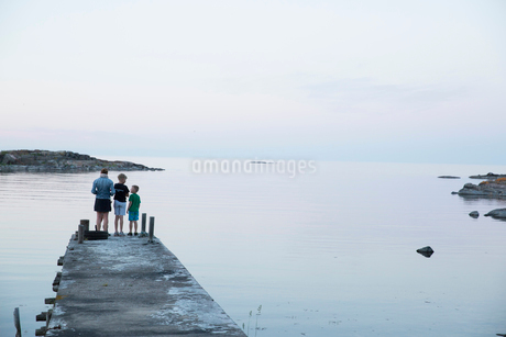 Mother and sons standing on a pier at Vaddo, Swedenの写真素材 [FYI02209447]