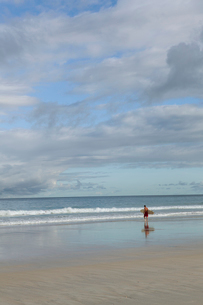 Man going for a surf at the beach in Broome, Australiaの写真素材 [FYI02209460]