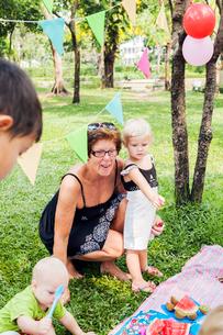 Grandmother with grandchildren at birthday picnicの写真素材 [FYI02209466]