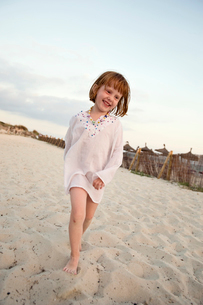 Spain, Majorca, Smiling redhead girl (4-5) walking barefoot on sandy beachの写真素材 [FYI02209491]