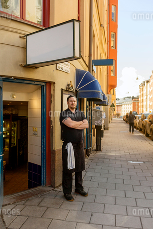 Fishmonger standing outside of storeの写真素材 [FYI02209541]