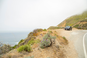 USA, California, Big Sur, Boy (14-15) and car by road overlooking seaの写真素材 [FYI02209543]