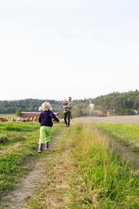 Man with his daughters on farm in Bergum, Swedenの写真素材 [FYI02209545]