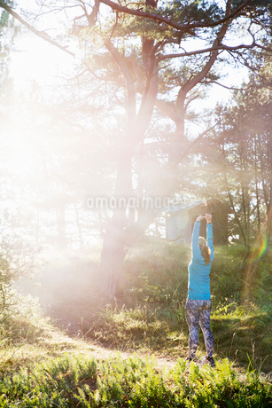 Woman stretching on forest path at Sandhammeren, Swedenの写真素材 [FYI02209546]