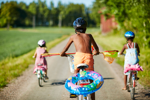 Children cycling on a rural road in Gullspang, Swedenの写真素材 [FYI02209549]