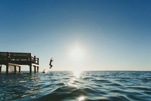 Two people jumping into the seaの写真素材 [FYI02209554]