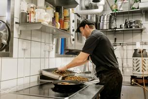 Fishmonger cooking in kitchenの写真素材 [FYI02209564]
