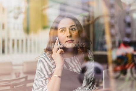 Barista using smart phone behind cafe windowの写真素材 [FYI02209568]