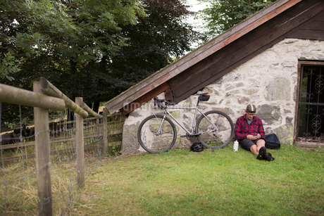 Mid adult man and bicycle leaning on a house in Lerum, Swedenの写真素材 [FYI02209585]