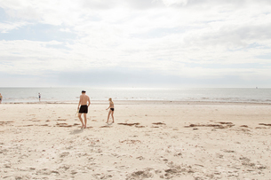 Man and girl walking on a beach in Osterlen, Swedenの写真素材 [FYI02209596]