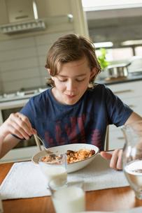 Teenage boy eating breakfast in a houseの写真素材 [FYI02209601]