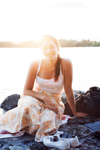 Young woman sitting in front of a lake in Dalarna, Swedenの写真素材 [FYI02209603]