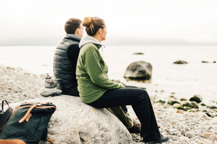 Couple sitting on rock on coastline at Sodermanland, Swedenの写真素材 [FYI02209609]