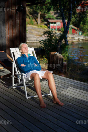 Sweden, Stockholm Archipelago, Sodermanland, Mefjard, Mature woman relaxing in deckchairの写真素材 [FYI02209615]