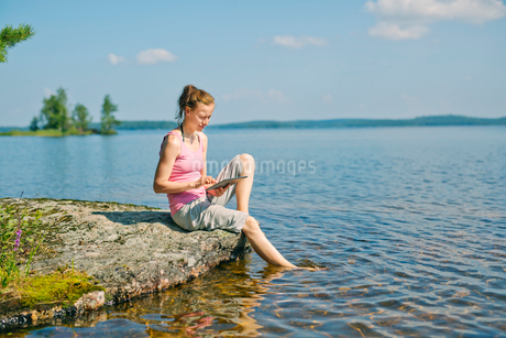 Mid adult woman looking at a tablet in front of a lake in Finlandの写真素材 [FYI02209618]