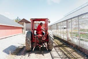 Garden centre worker on tractorの写真素材 [FYI02209640]