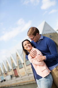 Sweden, Vastergotland, Smiling young couple against buildingsの写真素材 [FYI02209643]