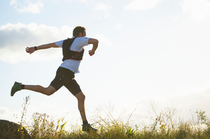 Man running through a field in Akersberga, Swedenの写真素材 [FYI02209651]