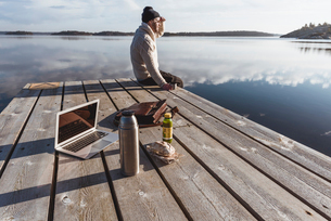 Man on pier next to laptop and lunch in Sodermanland, Swedenの写真素材 [FYI02209653]
