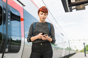 Woman looking at smart phone on train platformの写真素材 [FYI02209658]