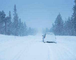 Car on rural road during winter in Dalarna, Swedenの写真素材 [FYI02209677]