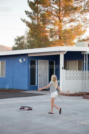 Girl walking to skateboard by houseの写真素材 [FYI02209686]