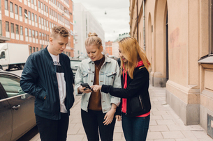 Teenagers look at a cell phone on a city street in Swedenの写真素材 [FYI02209688]