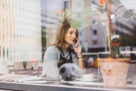 Barista using smart phone behind cafe windowの写真素材 [FYI02209705]