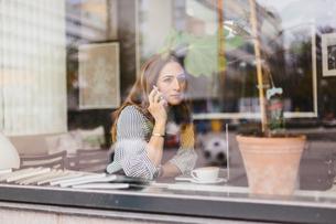 Barista using smart phone behind cafe windowの写真素材 [FYI02209730]