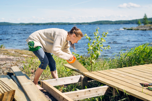 Mid adult woman building a deck in front of a lake in Finlandの写真素材 [FYI02209752]
