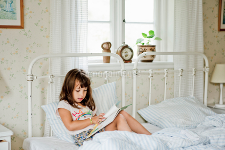 Girl reading in bedの写真素材 [FYI02209823]
