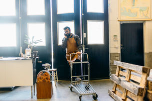 A coffee roaster talking on a cell phone and pushing a trolley in Swedenの写真素材 [FYI02209881]