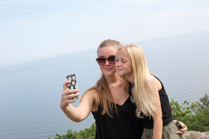 Sisters taking selfies with a cell phone in Osterlen, Swedenの写真素材 [FYI02209891]