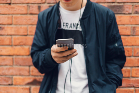 Teenage boy holding a cell phone in Swedenの写真素材 [FYI02209910]