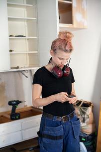 Sweden, Mid adult woman carpenter using phoneの写真素材 [FYI02209953]
