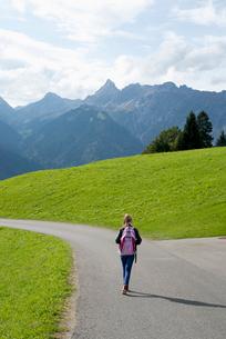 Girl walking along rural road in Vorarlberg, Austriaの写真素材 [FYI02210015]