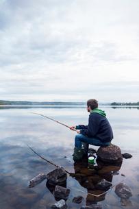 Mid adult man fishing on a lake in Dalarna, Swedenの写真素材 [FYI02210023]
