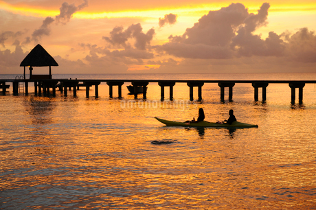 Man and woman kayaking at sunrise in Rangiroaの写真素材 [FYI02210055]