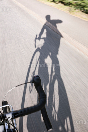 Man on bicycle casting shadow on road in Swedenの写真素材 [FYI02210096]