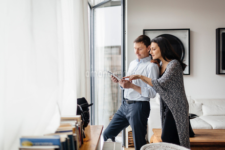 Germany, Couple using tablet by windowの写真素材 [FYI02210111]