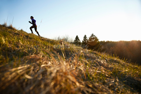 Woman running up a hill in in Akersberga, Swedenの写真素材 [FYI02210118]