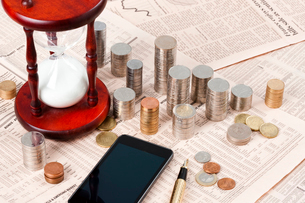 Coins, hourglass and smart phone on financial newspaperの写真素材 [FYI02210124]