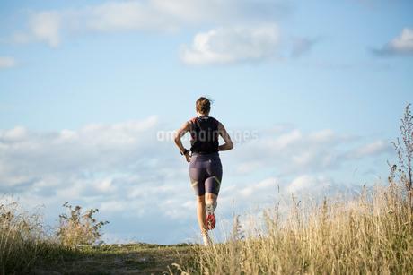 Woman jogging through field in Akersberga, Swedenの写真素材 [FYI02210125]